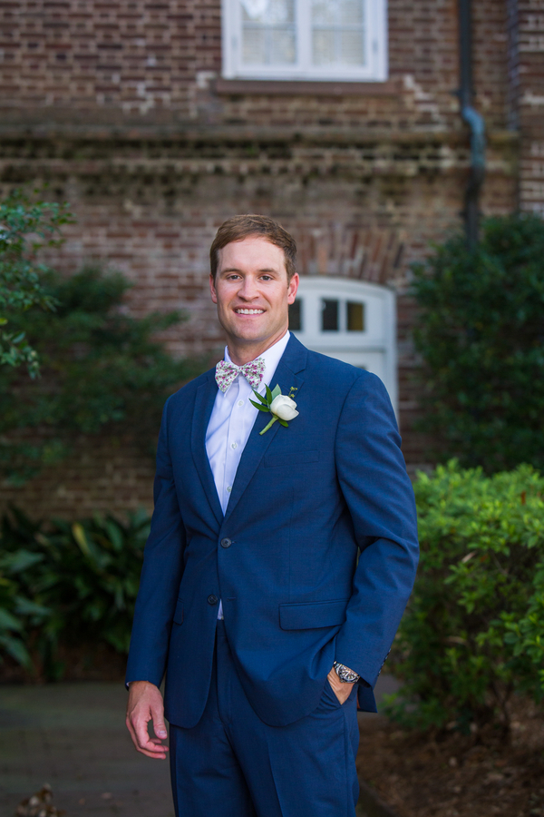 Groom in navy suit and bow tie at Rice Mill Building wedding in Charleston, SC