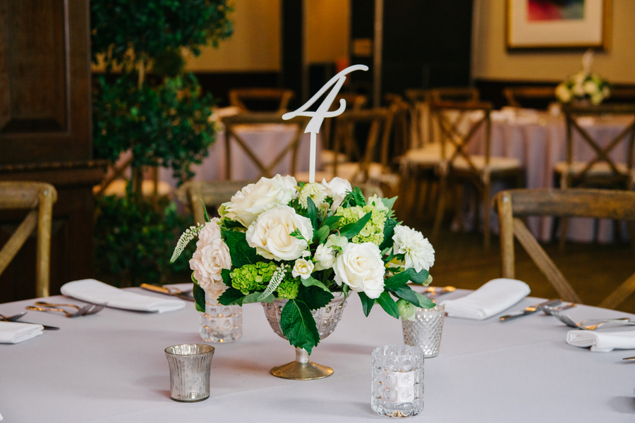 White roses and greenery centerpieces by Charleston Flower Market