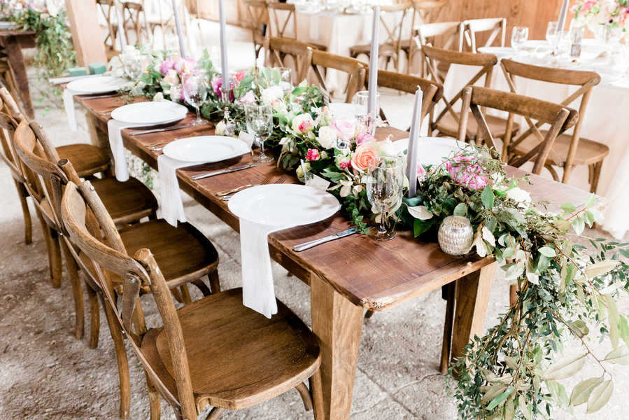 Farm tables with floral and greenery runner by Charleston Stems