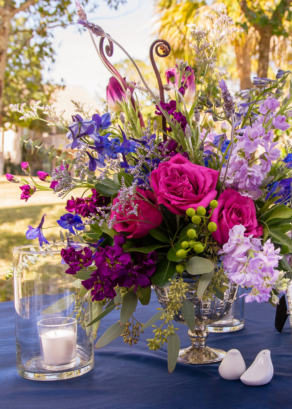Vibrant centerpieces of pink roses and blue delphinium by Gardenias Event Floral