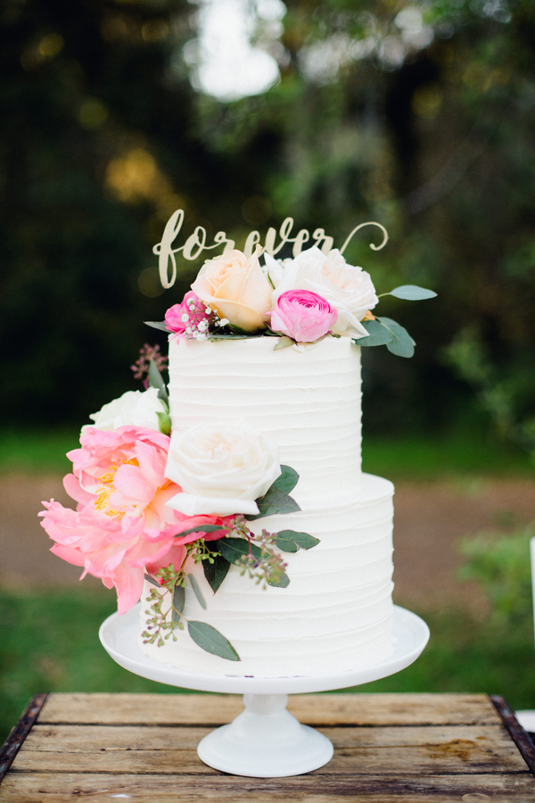 Elegant two-tiered white wedding cake with pink peony accents in Charleston, SC //  Charleston wedding cake on A Lowcountry Wedding Magazine & Blog
