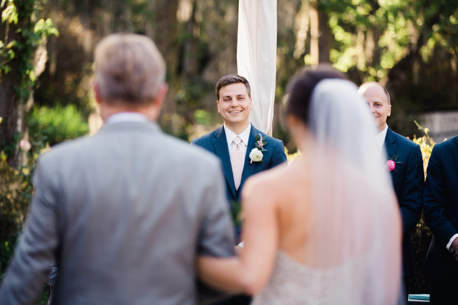 Groom watching his bride walk down the aisle at Magnolia Planation wedding in Charleston, SC // Charleston wedding photos on A Lowcountry Wedding Magazine