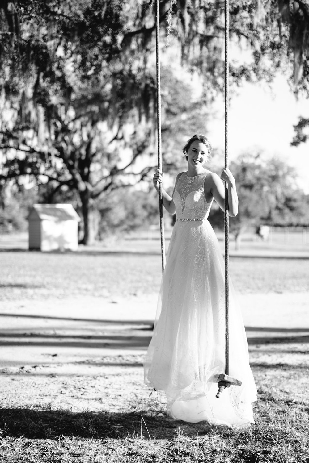 Bride on a swing in a Calle Blance Gown at Sugah Cain Plantation on Johns Island, SC  Bride and her maids at Sugah Cain Plantation in front of white horse and Carriage  //  on A Lowocountry Wedding Magazine & Blog