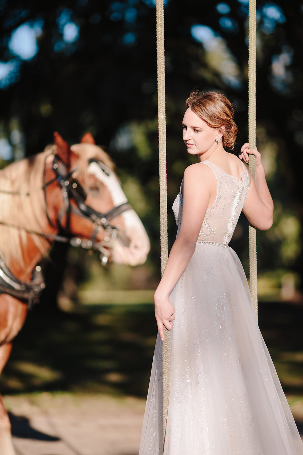 Bride on a swing at Sugah Cain Plantation with horse  Bride and her maids at Sugah Cain Plantation in front of white horse and Carriage  //  on A Lowocountry Wedding Magazine & Blog
