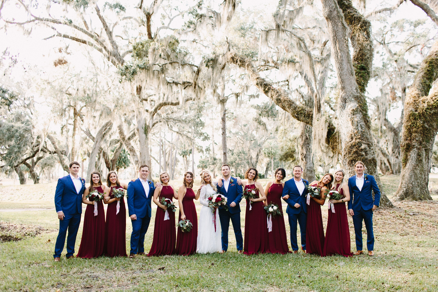 Bridesmaids in floor-length cranberry dresses and groomsmen in blue at King & Prince Resort on Saint Simons Island, Georgia