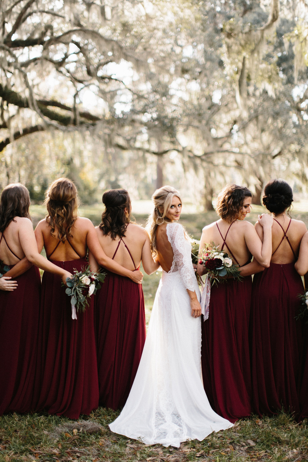 Bride in Grace Loves Lace dress, bridesmaids in floor-length cranberry dresses