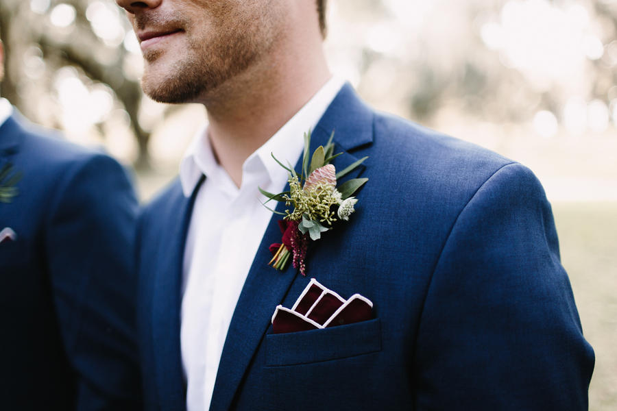 Groom in blue suit with cranberry pocket square and rustic boutonniere at King & Prince Resort wedding  //  Saint Simons Island, Georgia wedding venue  // A Lowcountry Wedding Magazine & Blog