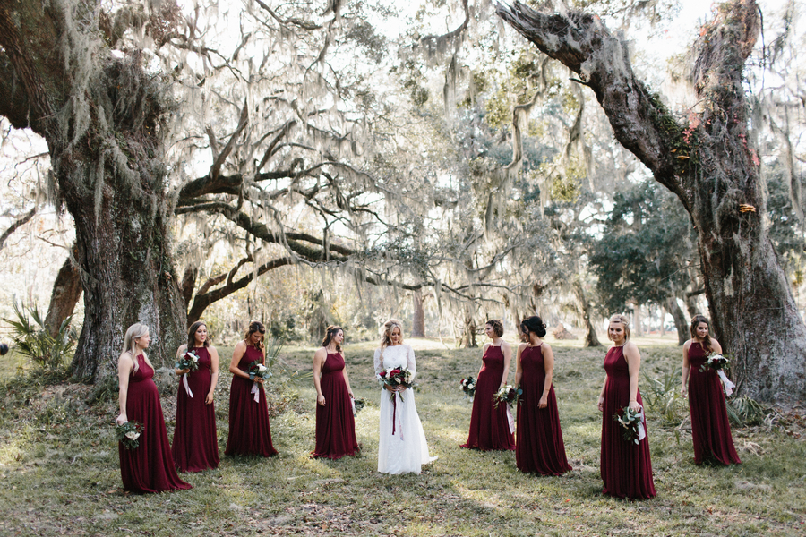 Bridesmaids in long cranberry dresses under the oak trees and Spanish moss on Saint Simons Island, Georgia  //  A Lowcountry Wedding Magazine & Blog