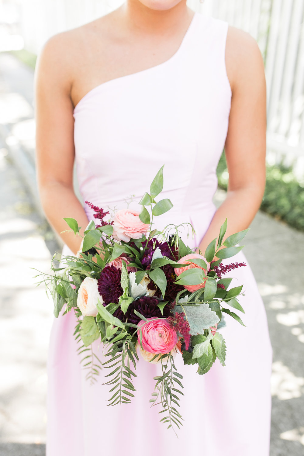 Bridesmaid wearing a one-shoulder pink LulaKate dress  Colorful outdoor reception at The Thomas Bennett House wedding in Charleston, SC  //  photographed by Jenna Weddings  Traditional wedding ceremony at Cathedral of St. John the Baptist in Charleston, SC  //  A Lowcountry Wedding Magazine & Blog