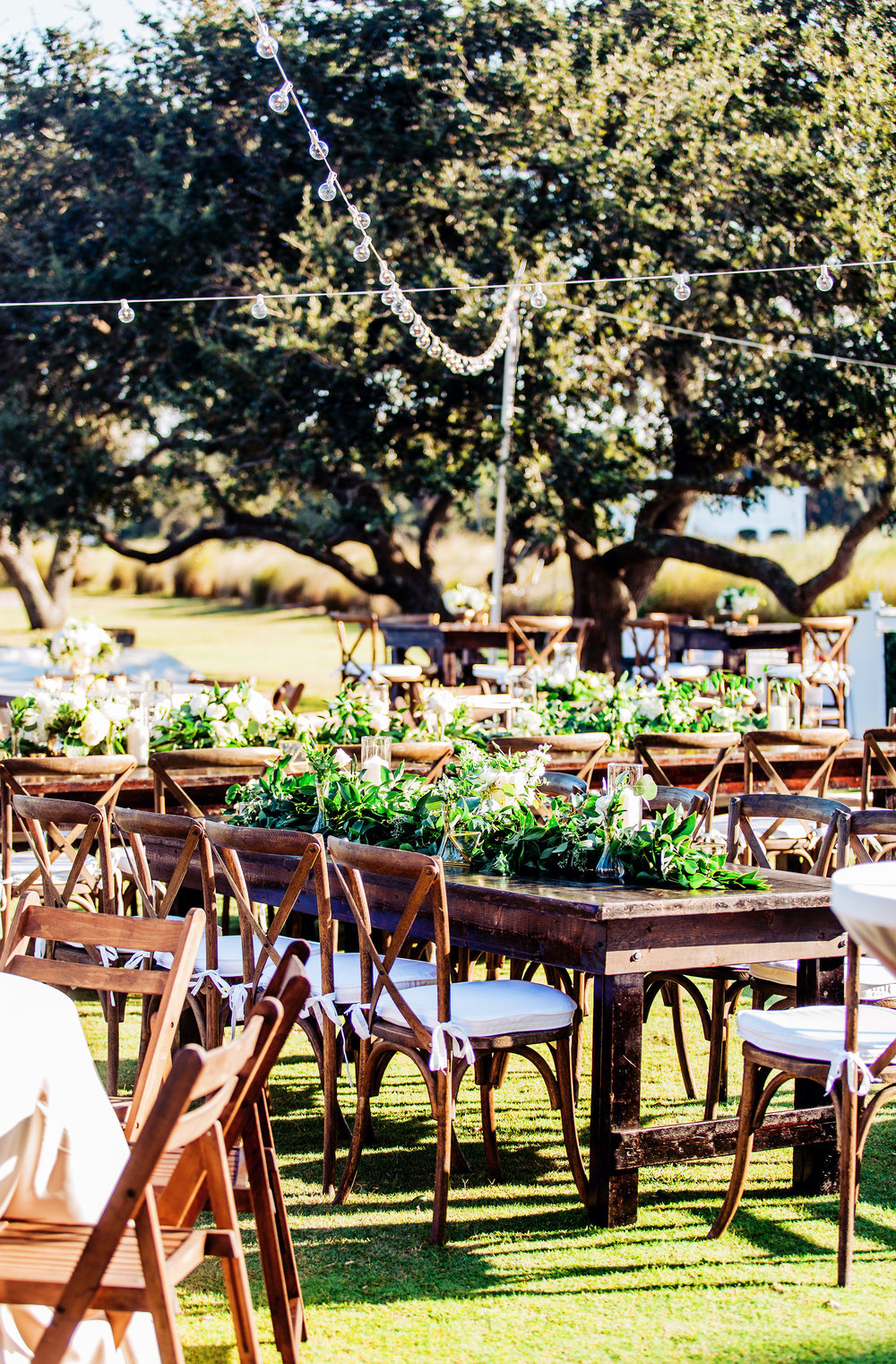 Greenery table runners on rustic farm tables with tall candles  //  A Lowcountry Wedding Magazine & Blog