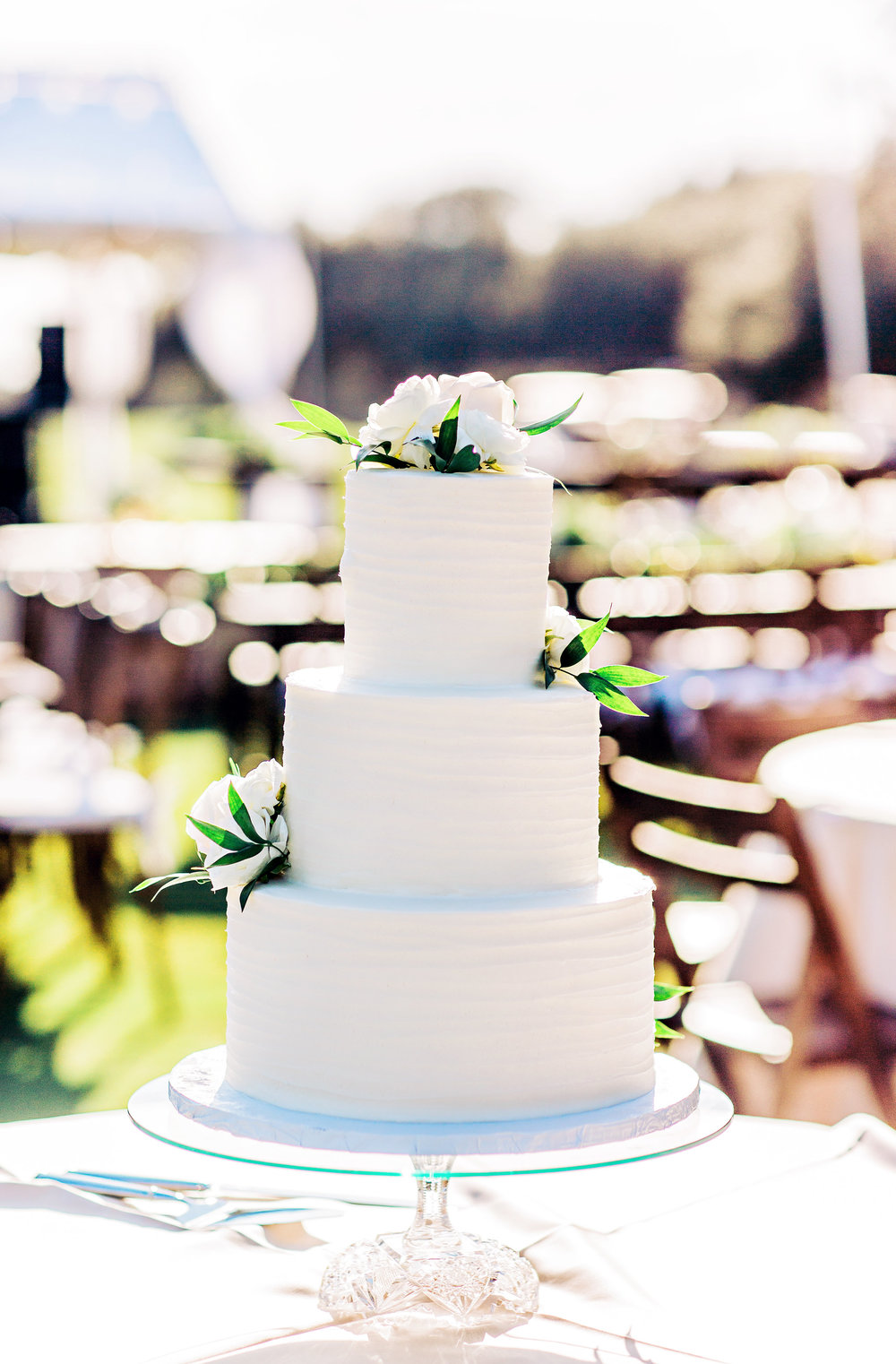 Three-tiered white cake at outdoor wedding reception at DeBordieu Club by Priceless Desserts