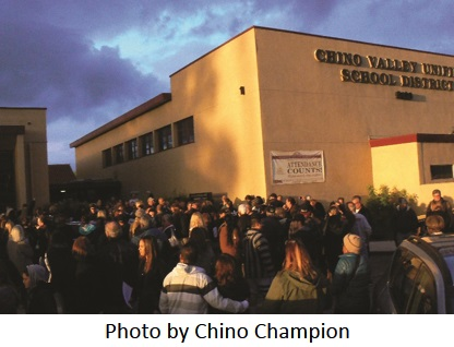 Crowd outside Chino Valley School District with caption