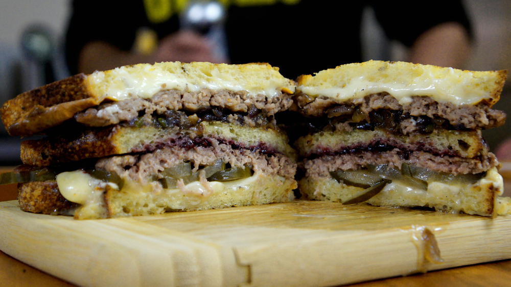 Amelia's semolina, Fischer Farms beef patty, house pickle made with Black Acre Saucy Intruder Rye IPA, Taleggio cheese, white American cheese, cipollini onion, jalapeno and Love Handle's berry jam.
