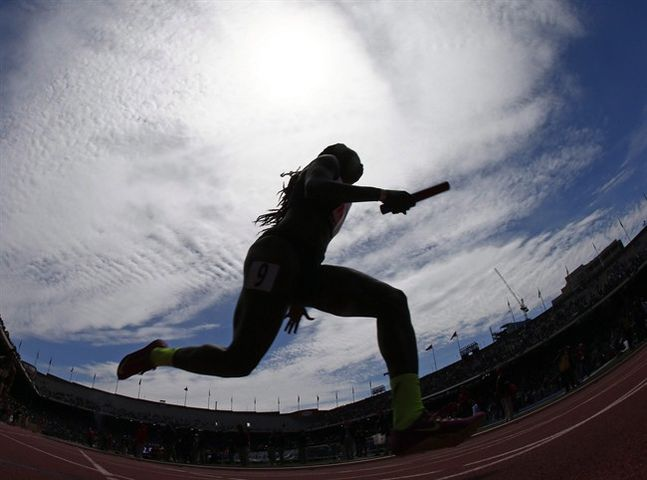 Sprinter Crystal Emmanuel of Canada is silhouetted as she runs in the USA vs. the World Women's 4x100 meter during the Penn Relays athletics meet, Saturday, April 25, 2015, in Philadelphia. Canada's Rio-bound women sprinters are giving the men a run for their money. THE CANADIAN PRESS/AP/Rich Schultz