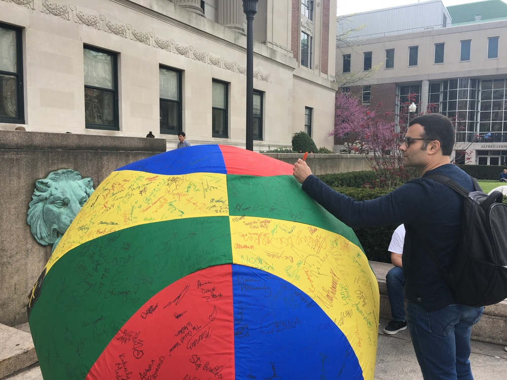 Murilo engaging in campus activism by signing this beach ball to donate money to the Children's Hospital at NewYork-Presbyterian/Columbia University Medical Center.