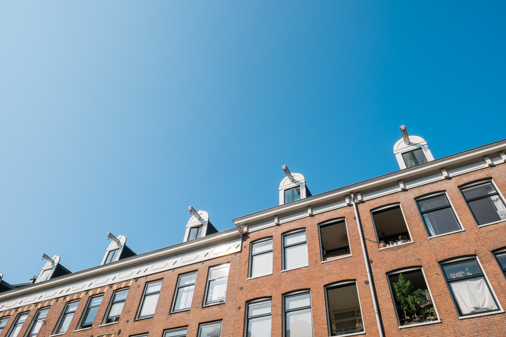The old homes and buildings lining the canals of Amsterdam have VERY narrow and steep staircases.  At the top of each building, you will most likely find a large arm with a hook.  This is so that large items can be hoisted to the upstairs floors (still in use today).