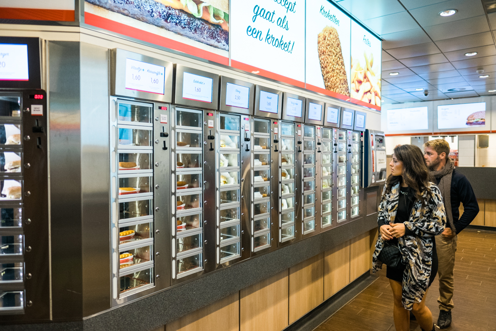 A wall of vending machines filled with late-night comfort food.  Each item costs around 1.60 euros - 3 euros.  Simply enter your coins, open the small door, and enjoy your food.