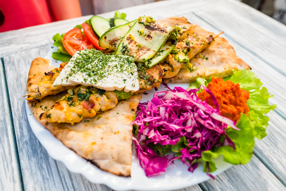 Pileci raznjici (grilled chicken skewers with cucumbers, tomatoes, pita bread, feta cheese, and a red bell pepper spread.