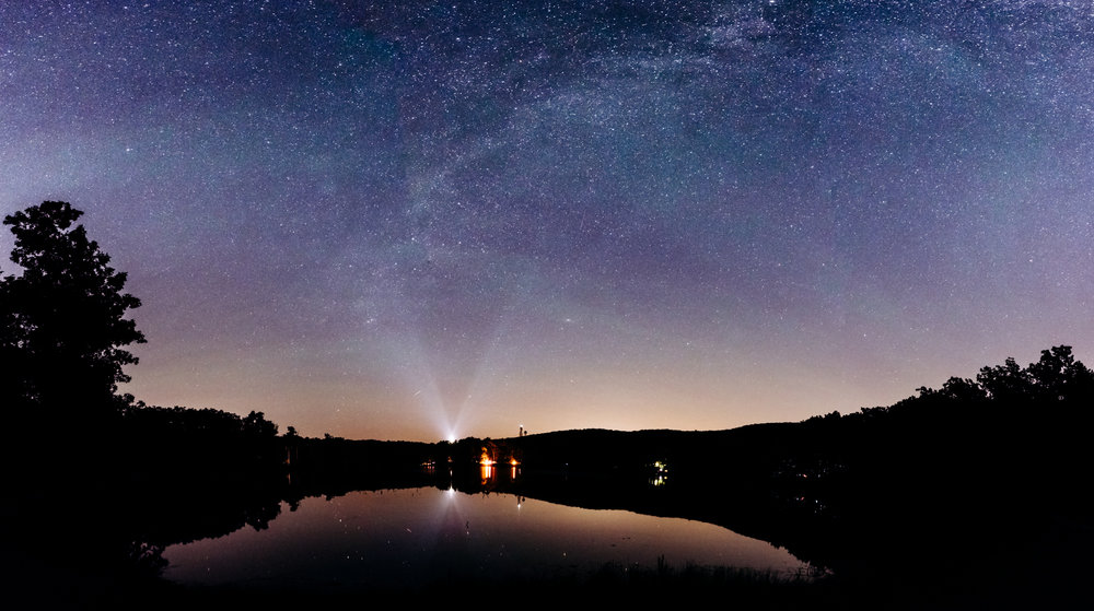 Light pollution is present even in some of the darkest parts of my home state of New Jersey. I was still able to capture a nice field of stars here by using 4 stitched vertical panoramic images using my favorite night photography lens, the Nikon 20mm f/1.8G