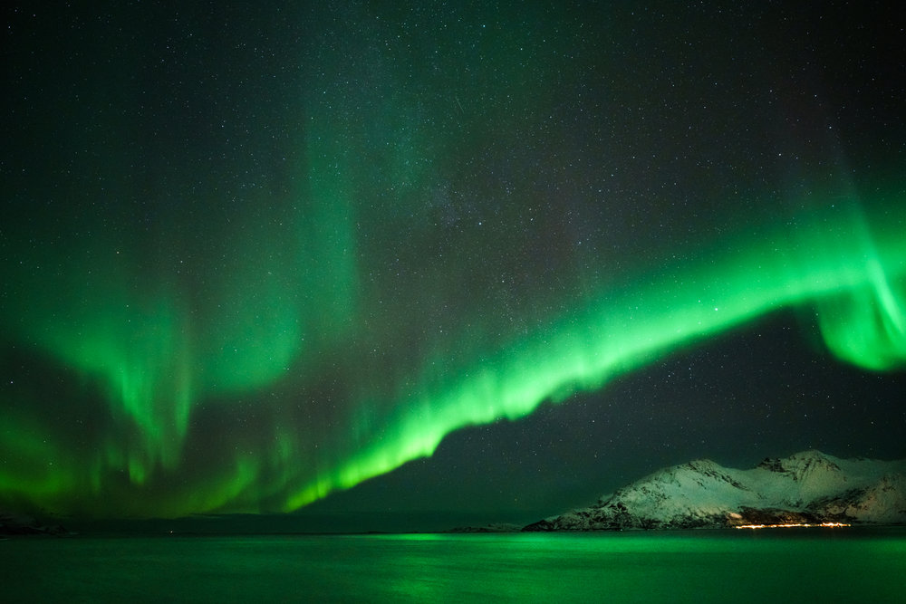 The water lit up to a bold green color on a relatively clear night near Rekvik, Norway.