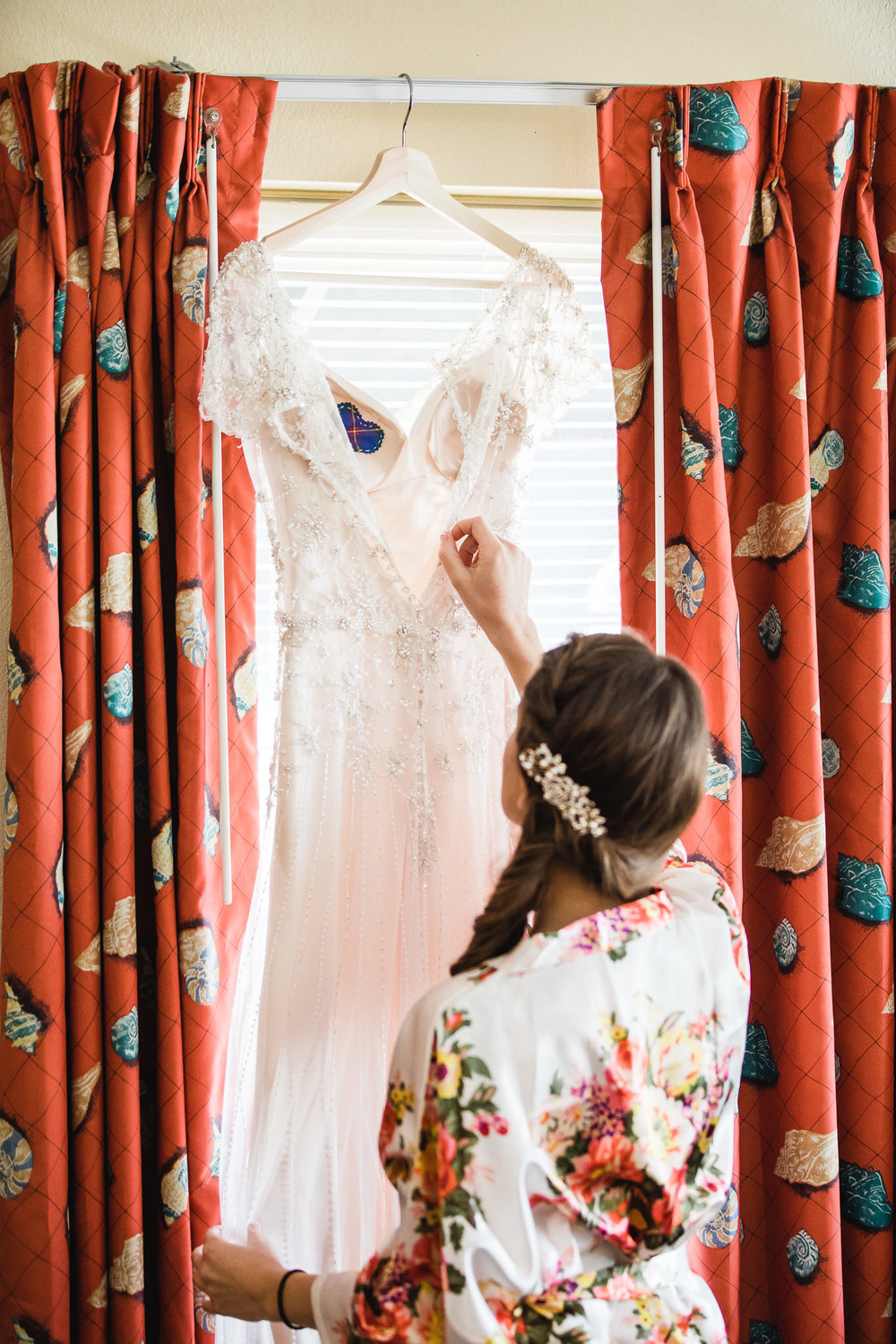 Wedding photograph of a bride looking at her dress at the Hollander Hotel in St. Petersburg, Florida
