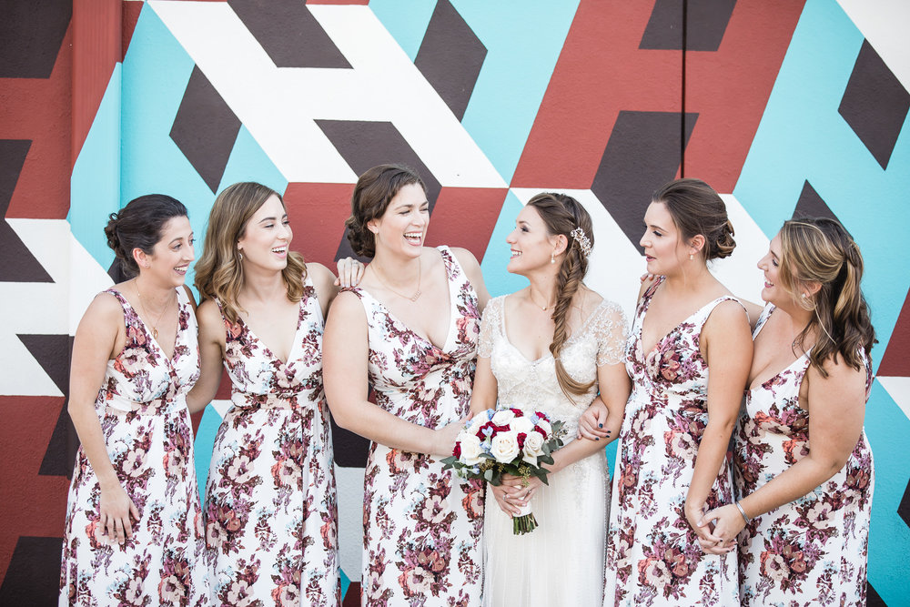 Photograph of bride and bridesmaids by artistic wall at the Hollander Hotel in St. Petersburg, Florida