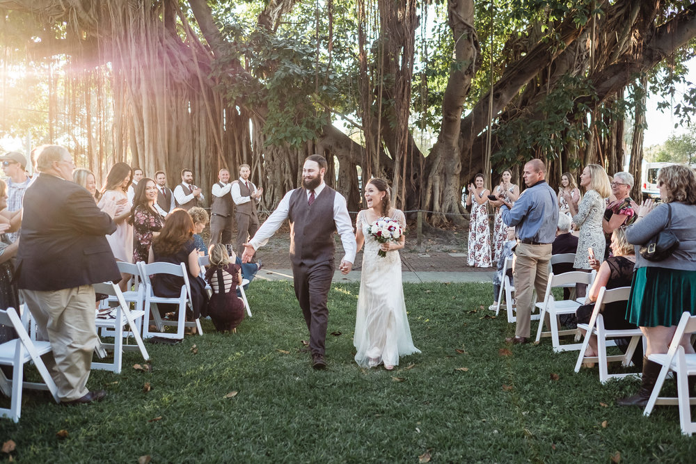 wedding photograph of a joyous bride and groom leaving their ceremony by a Banyan tree near Mirror Lake Park in St. Petersburg, Florida