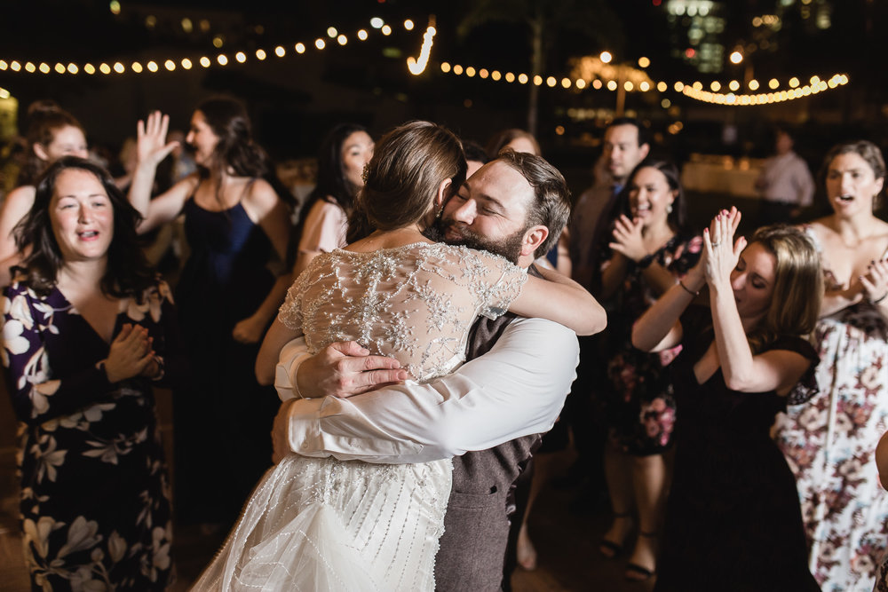 Fun nighttime wedding reception photograph of bride and groom hugging while dancing at The St. Petersburg Shuffleboard Club