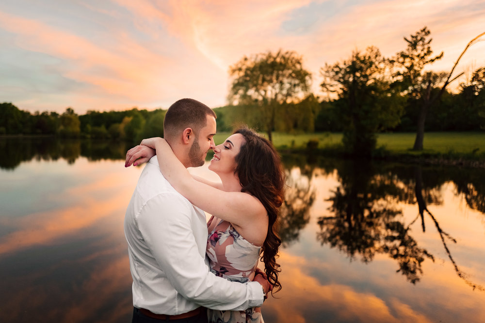 Engaged Couple Embracing and Touching Noses During an Orange and Blue Sunset sky at Verona Park New Jersey