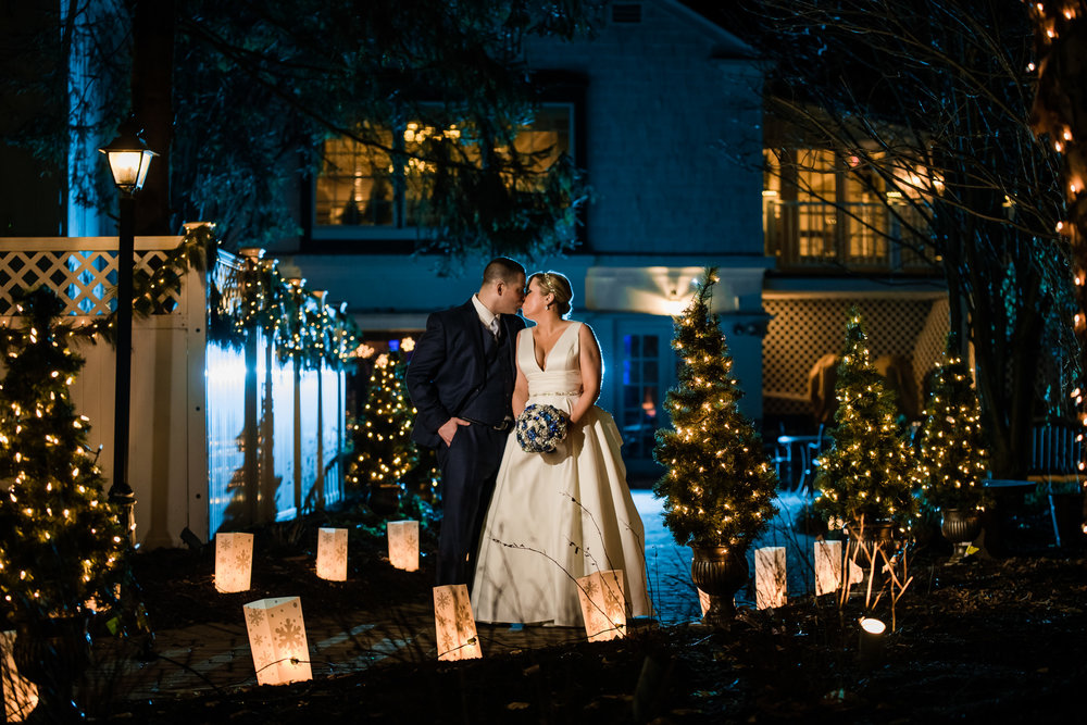 Bride and groom kissing during their winter wedding at the grain house in basking ridge new jersey with blue and orange Christmas themed lights