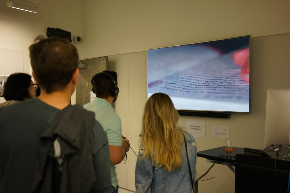 Guests observing video work by Raquel Salazar (class of 2019).