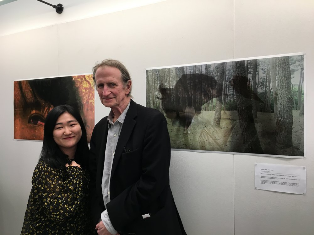 Youwon Jeong (class of 2018) with faculty member Ed Bowes, standing besides still from her thesis film.