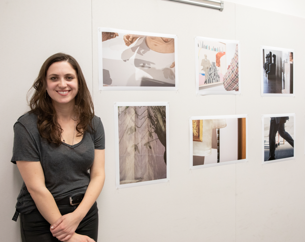 Nina Cochran (class of 2020) standing beside her photographic works.