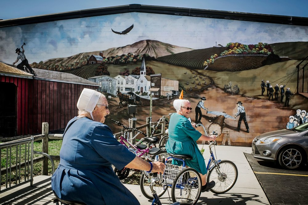 Two women pass by a mural depicting the ideal of the Amish life back home.