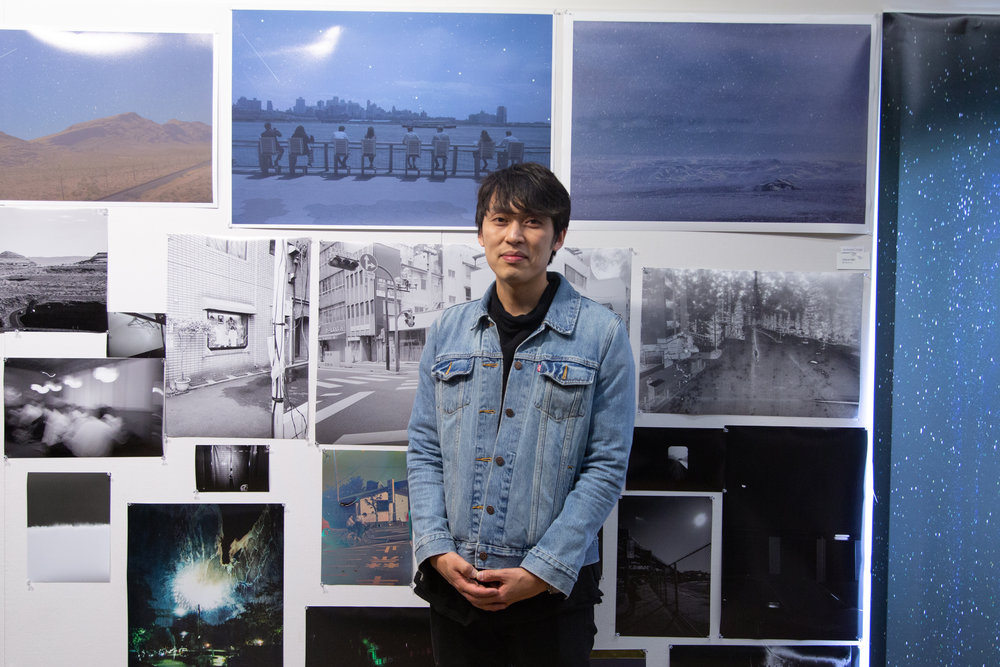 Wanki Min  standing beside a consortium of work from his ongoing series.