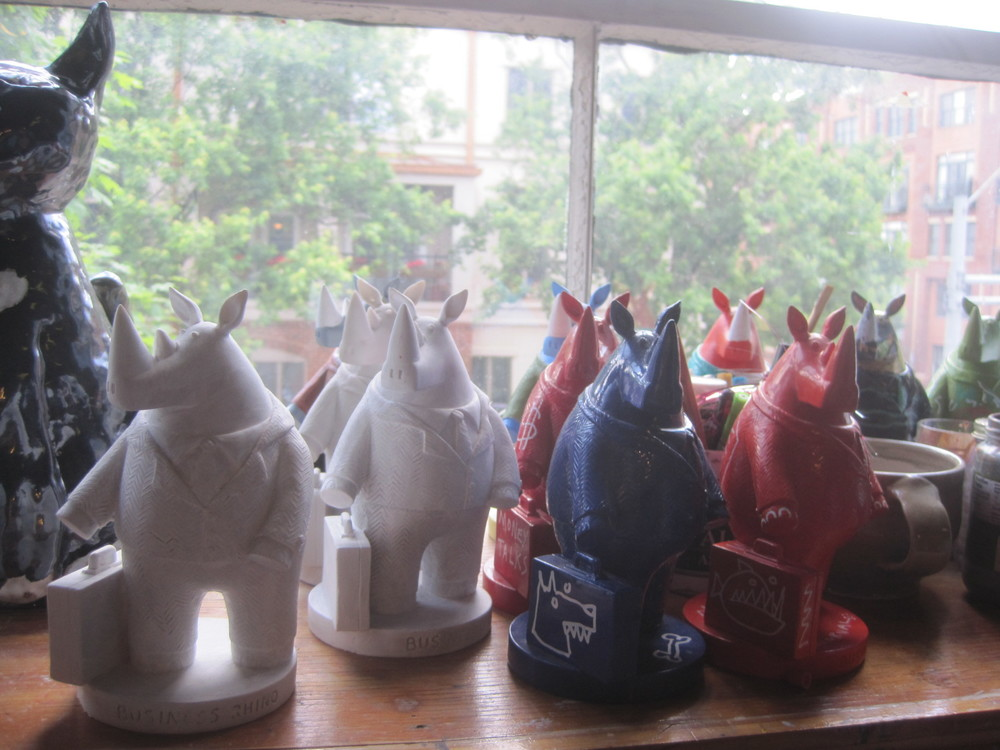 Some rhino sculptures at the studio. These Rhinos are manufactured to my specifications. Some come factory painted, and some are handprinted by me. On the left are the rhinos that await being hand-painted.