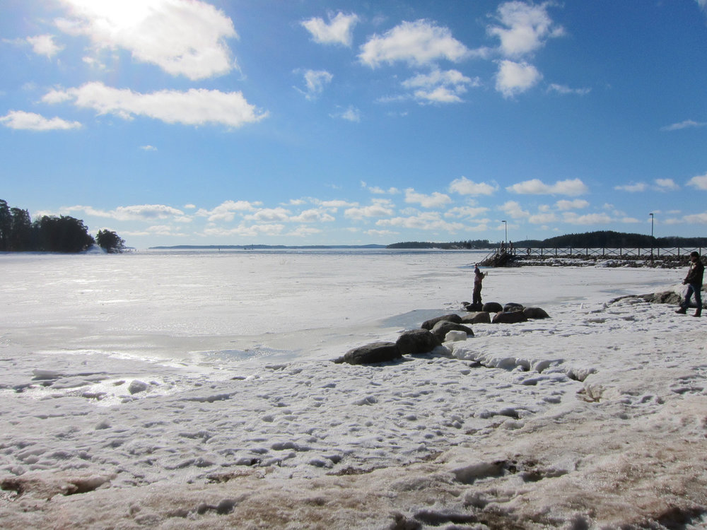 The frozen sea with the dock in the distant right.