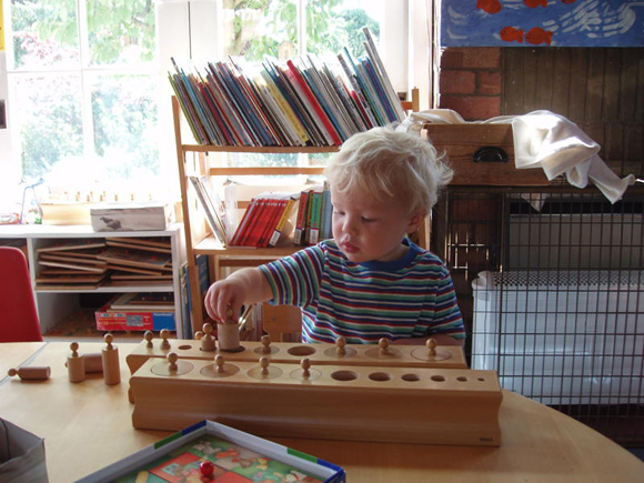 This boy is teaching himself about size and shape through use of this self correcting Montessori set of graduated cylinder blocks.