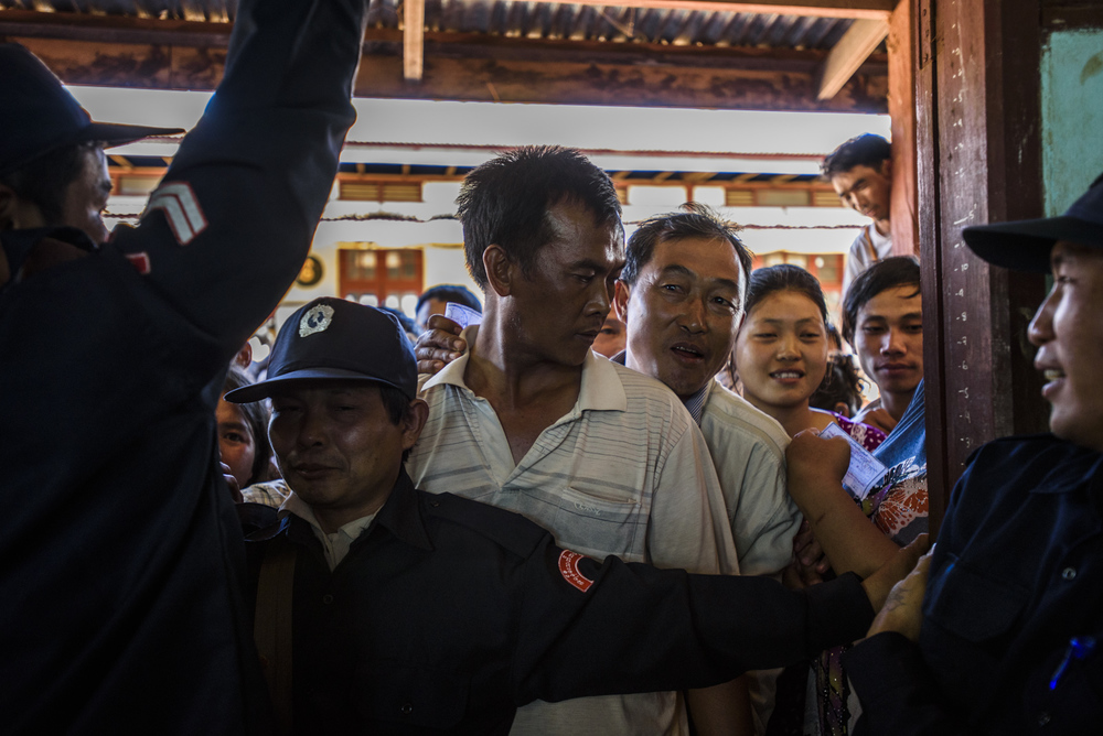 Security officers hold back a horde of voters at a polling station in One Leng's district in Lashio, Myanmar.