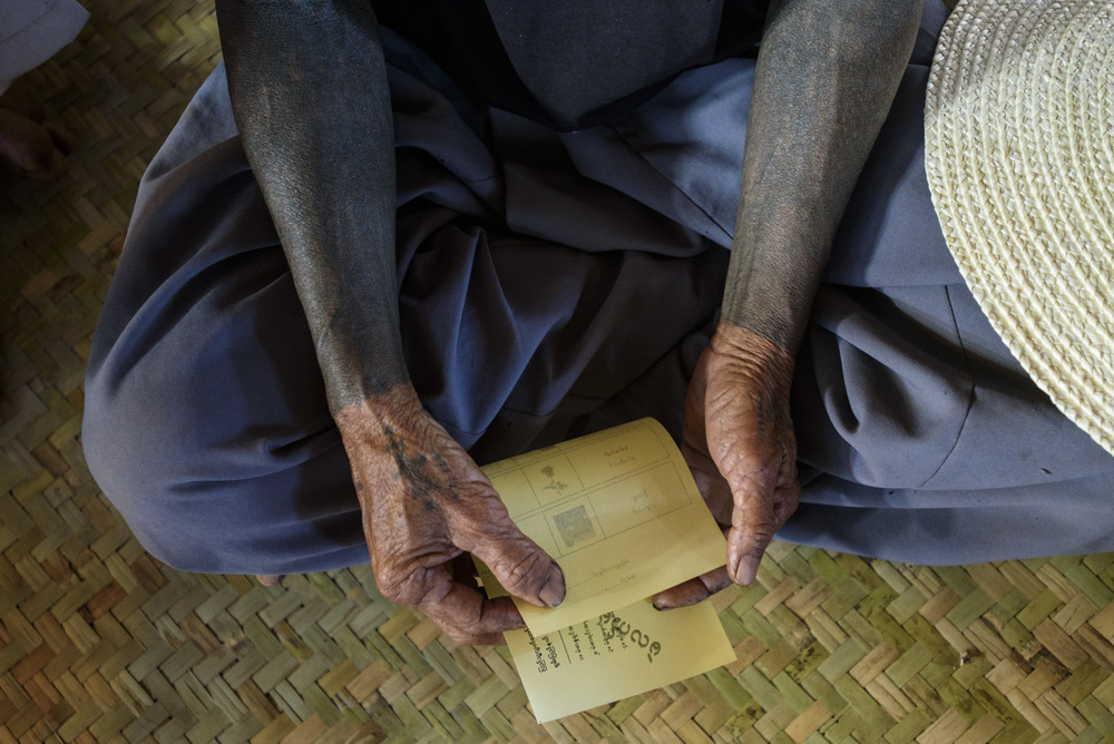 A villager with traditional Buddhist tattoos practices voting with a mock ballot. Many in the town, accessible only by a muddy mountain pass, will be voting for the first time.