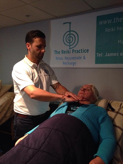 Reiki master James Graydon-Rhodes giving a Reiki treatment
