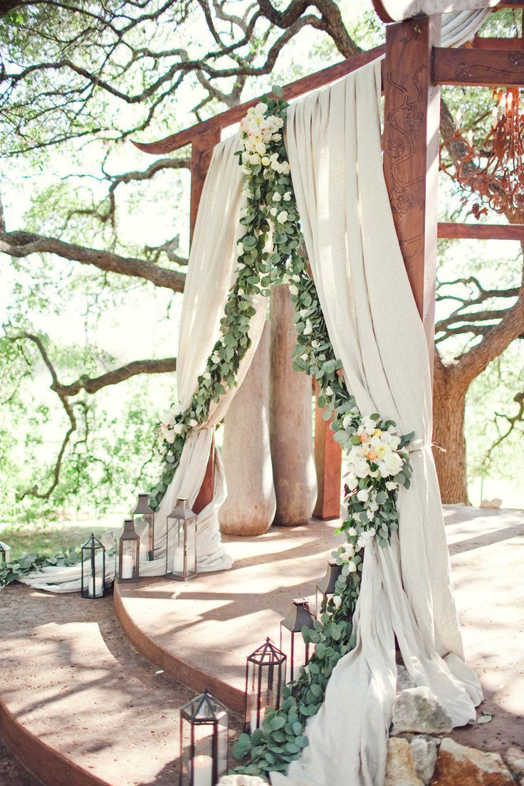Outdoor ceremony with fabric and floral garland draped over the arbor