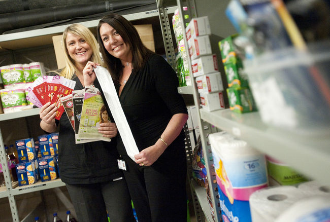 Tonia Richardson, left, holds coupons while Colleen Lindemann, right, holds a receipt for yogurt bought using coupons while in a storage locker where they store items they will donate to the London Food Bank at the Western Fair District, where they both work.(CRAIG GLOVER The London Free Pres)