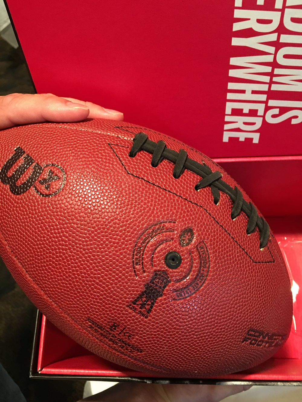 """The Wilson football factory's water tower in Ada, recently repainted with the NFL and Wilson logos, is embossed on Wilson's new """"connected"""" football."""
