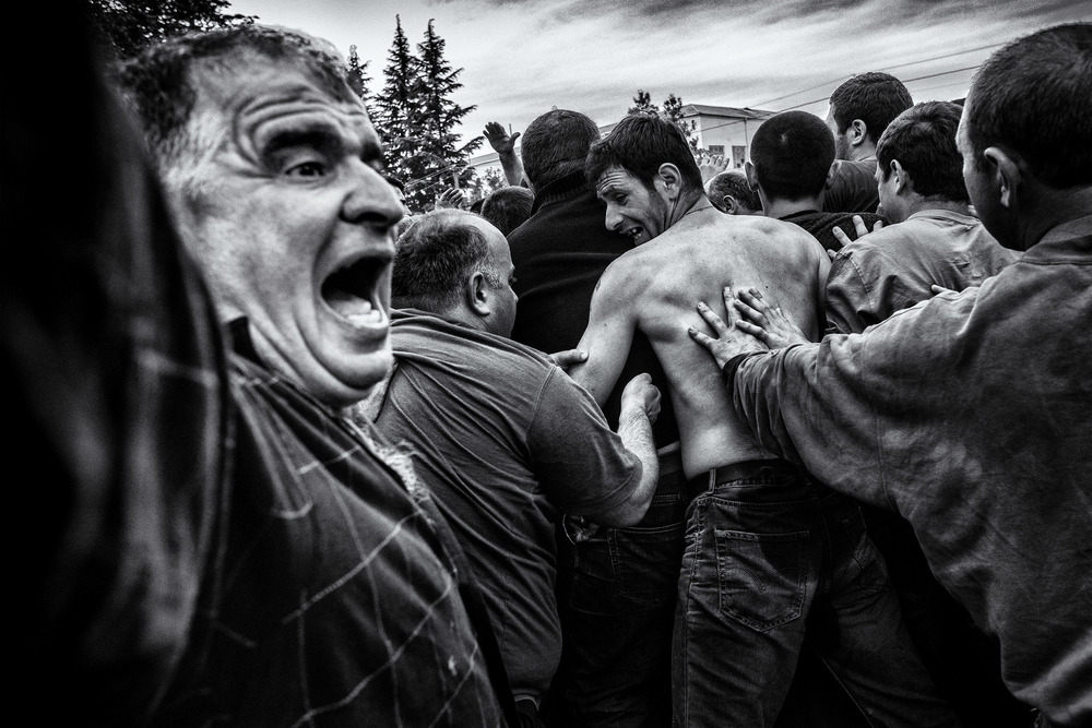 Usually the ball is not seen during the whole game as a melee is always on top of it. Despite its 16 kilo weight, men carried as it was a regular rugby ball. People falling, pushing, shouting. The brutality is part of the no rules game. Shukhuti, Georgia, April 2014.