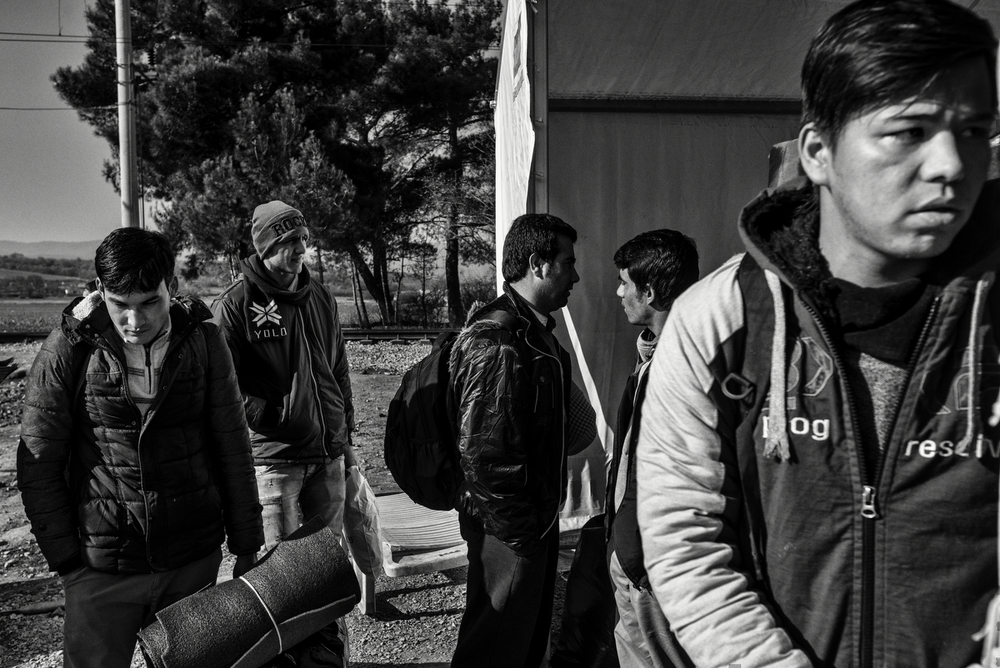 A group of afghans are waiting to cross the Greek-Macedonian border checkpoint in Idomeni. Greek police and Macedonian military has established a very tight control of the border, creating huge cues of people wanting to cross. After March 2016 this border cross has been closed. Idomeni, Greece, January 2016.