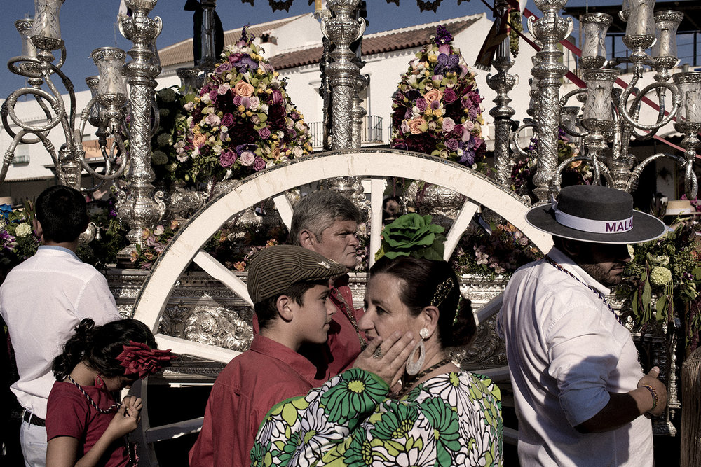 "Each brotherhood's ""simpecado"" wagon has to be carried in front of the hermitage to venerate the Virgin of El Rocío before Sunday's big ceremony. Despite the sandy roads and the high temperature most people doing the procession is wearing traditional andalusian costumes. El Rocío, Spain, May 2015."