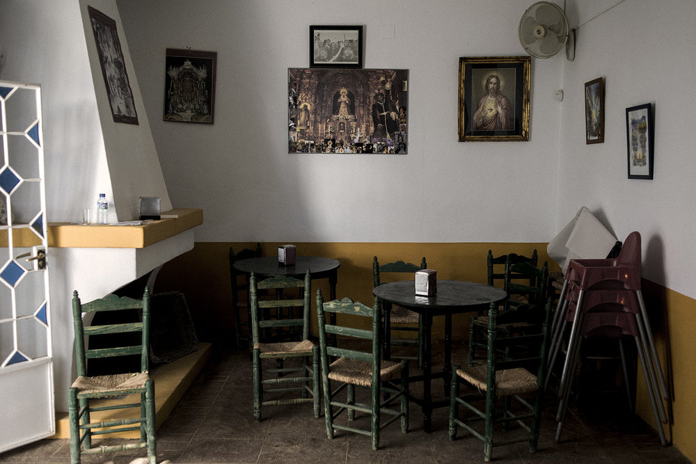 An inside view of a bar in El Rocío decorated with various catholic iconographies. Despite being inside one of the biggest  National parks in Spain, Doñana, this town focus all of its tourism during all year around religion. El Rocío, Spain, May 2015.