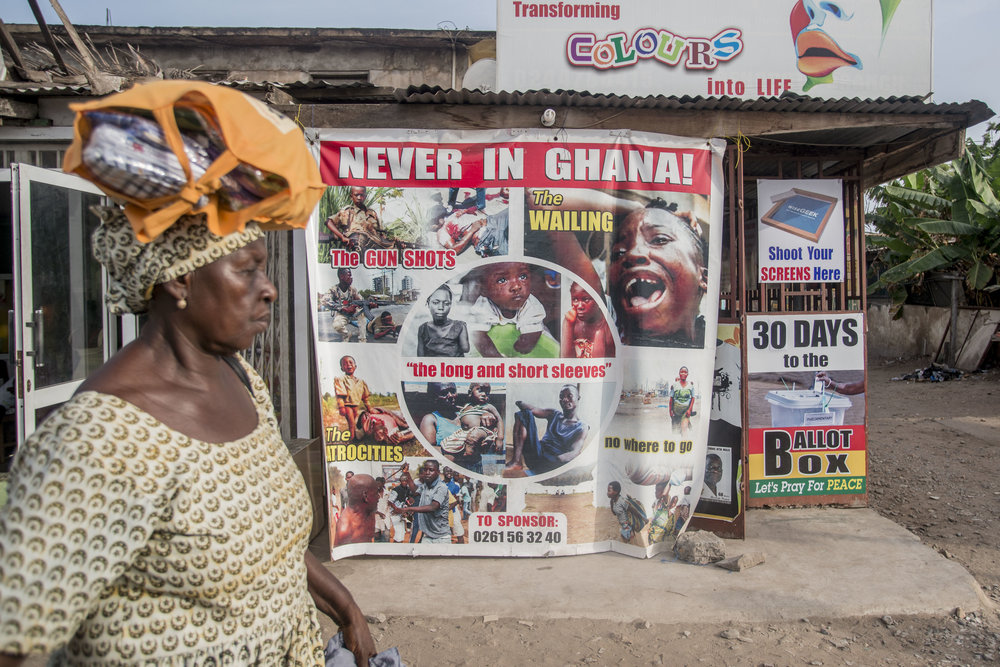 A woman pass by a billboard promoting the No Violence in Ghana. Being one of the oldest democracies in West Africa, Ghana prepares for the incoming general election on the 7th December. In various spots around the city of Accra countdowns for the elections can also be seen