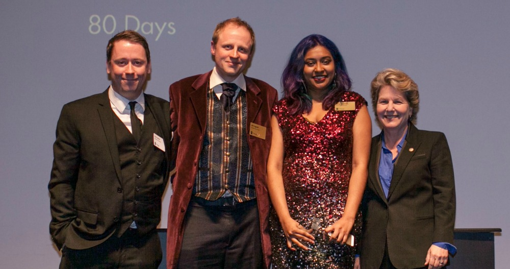 "Jon Ingold (center left) and 80 Days writer Meg Jayanth (center right) on stage together at the Writers Guild of Great Britain Awards, with Meg receiving the award for ""Best Writing in a Videogame"" for her work on 80 Days"